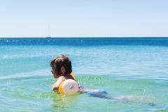 Meisje het baden met een vlotter op het strand stock afbeeldingen