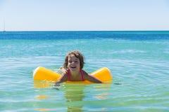 Meisje het baden met een vlotter op het strand stock fotografie