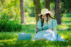 Meisje in het beeld van de heldin van een feezitting onder een boom royalty-vrije stock afbeelding