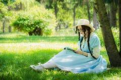 Meisje in het beeld van de heldin van een feezitting onder een boom royalty-vrije stock foto's