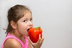 Meisje het bijten in een peper Stock Fotografie