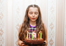 Meisje het blazen uit schouwt op de cake royalty-vrije stock foto
