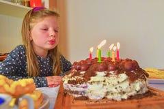 Meisje het blazen uit schouwt op haar verjaardagscake Klein meisje die haar verjaardag zes vieren Verjaardagscake en meisje royalty-vrije stock foto's