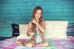 Meisje het borstelen haar in slaapkamer royalty-vrije stock afbeeldingen