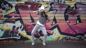 Meisje het dansen tektoniek in de straat tegen de achtergrond van graffiti stock video