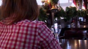 Meisje het drinken glas een donker bier in een restaurantzitting terug naar camera stock videobeelden