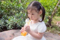 Meisje het drinken jus d'orange van fles door stro Stock Afbeelding
