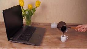 Meisje het drinken koffie in de keuken Op de keukenlijst naast het laptop meisje die verse koffie drinken Zij snuift het aroma va stock footage