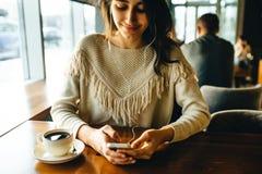 Meisje het drinken koffie en het luisteren aan muziek in de koffie royalty-vrije stock afbeeldingen