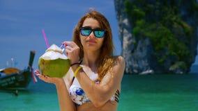 Meisje het drinken van kokosnoot op een tropisch strand stock video