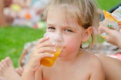 Meisje het drinken vruchtensap van een plastic beschikbare kop en onderzocht het kader Royalty-vrije Stock Fotografie