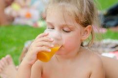 Meisje het drinken vruchtensap van plastic beschikbare kop Royalty-vrije Stock Afbeelding