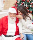 Meisje het Fluisteren Wens in het Oor van de Kerstman Stock Foto