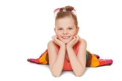 Meisje het glimlachen in kleurrijke rok ligt Gelukkig die kind met handen dichtbij gezicht, op witte achtergrond wordt geïsoleerd stock foto