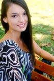 Meisje het glimlachen zitting op een bank in het park. Royalty-vrije Stock Foto's