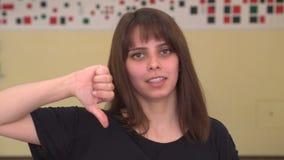 Meisje het Grijnzen voor Camera en geeft neer Duimen stock footage