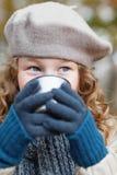 Meisje in het grijze baret drinken van fleskop stock foto
