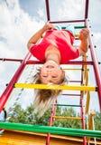 Meisje het hangen van een wildernisgymnastiek die in een de zomertuin spelen - concept van het kind het gewaagde spel royalty-vrije stock fotografie