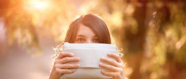 Meisje het hidding door een beurs te houden Stock Afbeeldingen