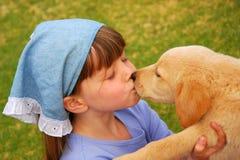 Meisje het kussen puppy Stock Afbeeldingen