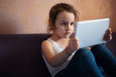 Meisje het letten op beeldverhalen op de tablet royalty-vrije stock fotografie