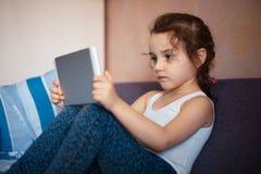 Meisje het letten op beeldverhalen op de tablet stock foto's