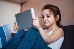 Meisje het letten op beeldverhalen op de tablet stock foto