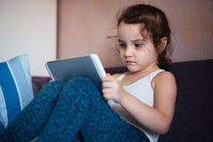 Meisje het letten op beeldverhalen op de tablet stock afbeeldingen