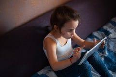 Meisje het letten op beeldverhalen op de tablet royalty-vrije stock afbeeldingen