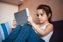 Meisje het letten op beeldverhalen op de tablet royalty-vrije stock foto