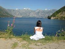 Meisje het letten op bergen en het overzees stock foto