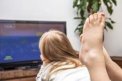 Meisje het letten op televisie op de bank stock afbeeldingen