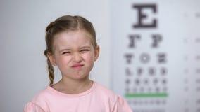 Meisje het loensen ogen, die aan vage visie, diagnostiek lijden van astigmatisme stock footage