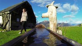 Meisje het lopen door fontein met panoramisch alpen scène stock videobeelden