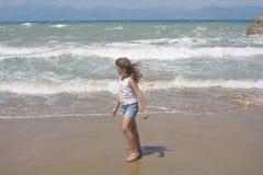 Meisje het lopen en kijkt op de overzeese golven Stock Afbeelding
