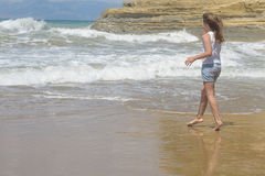Meisje het lopen en kijkt op de overzeese golven Royalty-vrije Stock Afbeeldingen