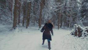 Meisje het lopen in het de winterbos dat zij heeft gedraaid, wervelt en werpt sneeuw stock video