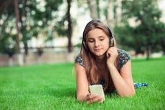 Meisje het luisteren aan wat muziek die interessant telefoonbericht bekijken dat zij heeft ontvangen stock foto