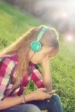 Meisje het luisteren muziek op de weide in uitstekende stijl royalty-vrije stock fotografie