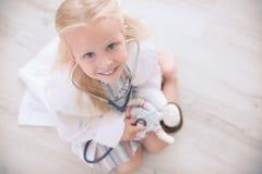 Meisje in het medische laag spelen met pop Stock Afbeeldingen