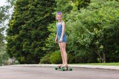 Meisje het met een skateboard rijden Stock Afbeeldingen