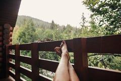 Meisje het ontspannen in houten plattelandshuisje op portiek onder hout De benen van de vrouw royalty-vrije stock afbeelding