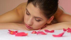 Meisje het ontspannen na massage die op handdoeken met roze bloemblaadjes liggen stock footage