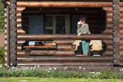 Meisje het ontspannen op de portiek van het Chalet royalty-vrije stock afbeelding