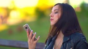 Meisje in het Park die een broodje, de telefoonringen eten Zij verbetert stock video