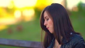 Meisje in het Park, die op de telefoon spreken Zet de telefoon neer, begint een broodje te eten stock footage
