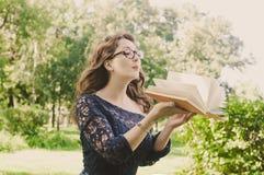 Meisje in het park met een boek Stock Foto's