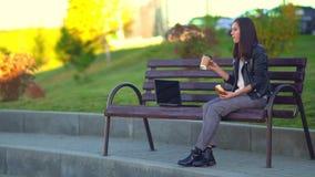 Meisje in het Park op een bank die, die van het werk rusten en een snack maken Het eten van een scone stock videobeelden