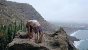 Meisje het praktizeren yoga op de rotsen tegen de blauwe hemel en het azuurblauwe overzees Vrouwentribunes op een steen in een br stock videobeelden