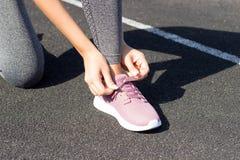 Meisje het rijgen op zijn Roze tennisschoenen voor het lopen geen gezichtsclose-up In openlucht, zonlicht, stadion, sport en fitn royalty-vrije stock foto's